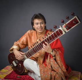 Picture of Indian musician Ustad Shafaat Kahn playing sitar.