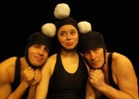Three performers of Galumpha are shown here with silly grins and balls on their heads.