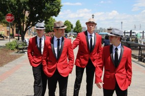 The Jersey Tenors singing group are shown walking down a street in red jackets and white hats.