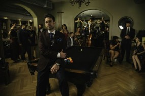 Photo shows the group Postmodern Jukebox standing around a billiards table.