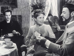 Two men and a woman are in a parlor in a scene in Ingmar Bergman's Smiles of a Summer Night.