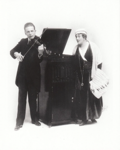 """A picture, taken in 1918, of two of the most famous Edison Tone Test musicians, Albert Spalding and Marie Rappold, performing with an Edison phonograph as part of a Tone Test (""""Edison Phonograph Tone Test"""")."""