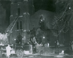 Photograph of firefighters on the scene at St. Francis De Sales Church, which was set on fire April 10, 1965. Image courtesy of the Geneva Public Library and the New York Heritage Digital Collection. https://cdm16694.contentdm.oclc.org/digital/collection/JSY/id/27.