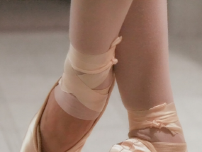 A dancer wears ballet slippers