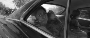 Black and white photo of a woman holding a child in the back of a car