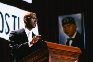 Malcolm X stands at a podium