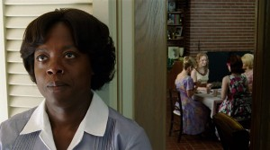 A table of white women are in the background as a black maid stands in the foreground