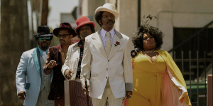 Eddie Murphy and other cast members walk down the street in Dolemite is My Name