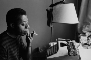 James Baldwin sits in front of a type writer