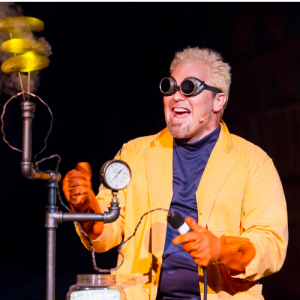 Doktor Kaboom performs on stage with an apparatus and wearing dark goggles