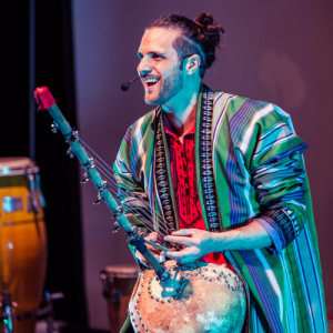 Percussionist Kattam holds one of his instruments on stage