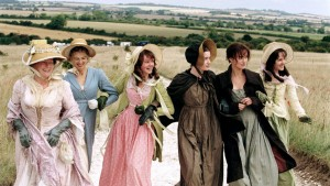A group of women, dressed in 18th century clothing, lock arms and stroll along a hillside. Keira Knightly stars in Pride + Prejudice.
