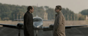 Two men converse in front of a spy plane in Tinker Tailor Soldier Spy