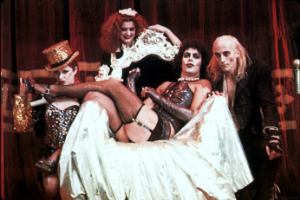 The cast of Rocky Horror Picture Show pose around a throne like chair draped in white cloth.