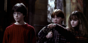 Daniel Radcliffe, Rupert Grint, and Emma Watson (holding a wand) star in Harry Potter and the Sorcerer's Stone