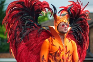 Taron Egerton as Elton John, wears a flamboyant orange costume with large red wings for Rocketman