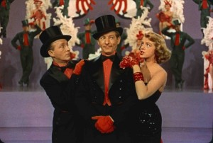Danny Kaye, stands in the middle dressed in a black suit with a red shirt and black top hat as Bing Crosby, dressed in the same outfit, and Rosemary Clooney wearing a strapless black dress, stand to the side of him.