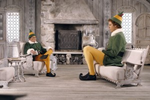 Two men dressed as Santa's elves sit in a room, one fitting into the furniture and the other oversized and giant like