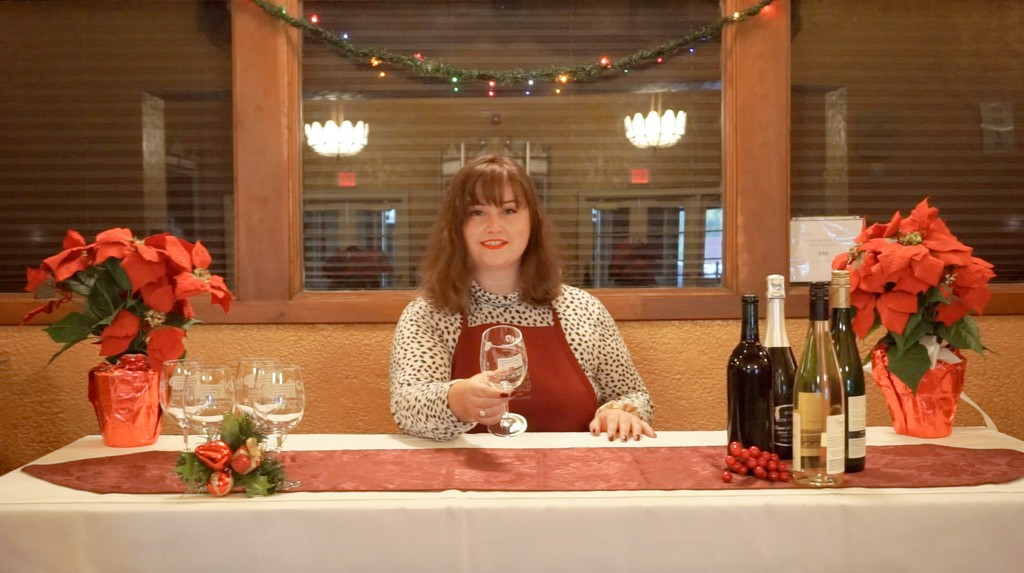 A woman with short brown hair poses at a wine bar set up in the Smith's lobby. Christmas garland is hung behind her as she offers a glass to the camera.