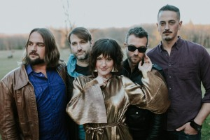 Maddy Walsh stands center in dark brown hair and a metallic gold blouse, while her male backing band The Blind Spots stand behind her