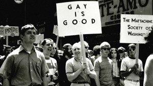 LGBTQIA+ Activists march for equality. One male activist holds a sign that says 'Gay is Good'.
